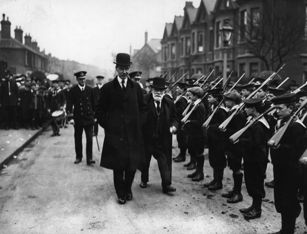 circa 1920: British politician Andrew Bonar Law inspecting a troop of boys at the Victoria Club in Kew. Bonar Law worked in a Glasgow iron yard before beginning his political career as a Unionist MP. He succeeded Lord Balfour as Unionist leader in the House of Commons (1911) and served as a member of the War Cabinet, Chancellor of the Exchequer and Lord Privy Seal before becoming the leader of the House of Commons. He retired in March 1921 due to ill health but returned to be Prime Minister in 1922. (Photo by Topical Press Agency/Getty Images)