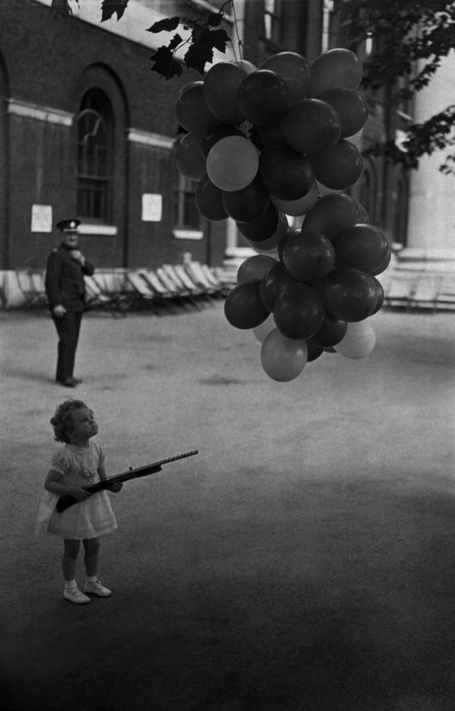 23rd June 1937: A young guest at the Children's Coronation Garden Party, at the Duke of York's headquarters, London, seen here deciding which balloon to burst with her pop gun. (Photo by E. Dean/Topical Press Agency/Getty Images)