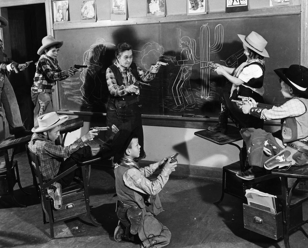 circa 1950: Arizona schoolchildren dressed as cowboys playing out a shoot-out in the classroom with their teacher. (Photo by Three Lions/Getty Images)