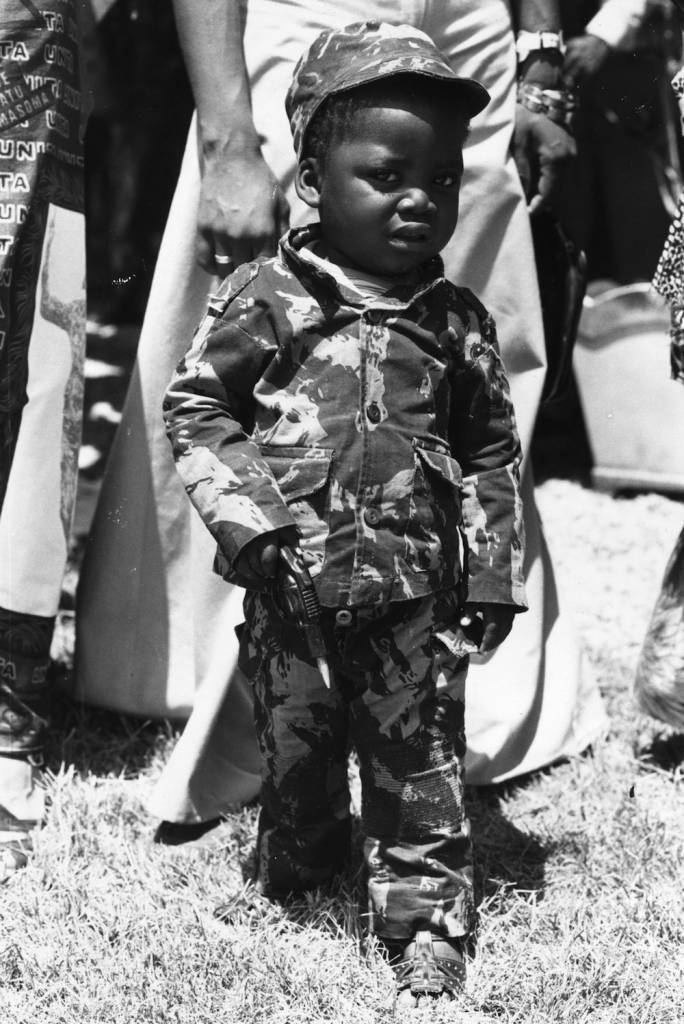 13th November 1975: A toddler dressed in battle dress and holding a toy gun, at the giant rally held in the Nova Lisboa football stadium to celebrate the independence of Angola. (Photo by Keystone/Getty Images)