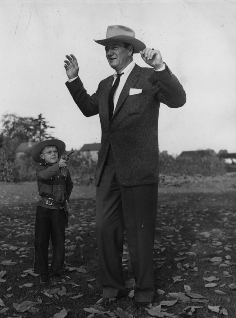 28th October 1960: Seven-year-old Jeremy Seaward holds up American film actor John Wayne during Wayne's visit to the Invalid Children's Aid Assoiation's Meath School at Ottershaw. (Photo by Keystone/Getty Images)