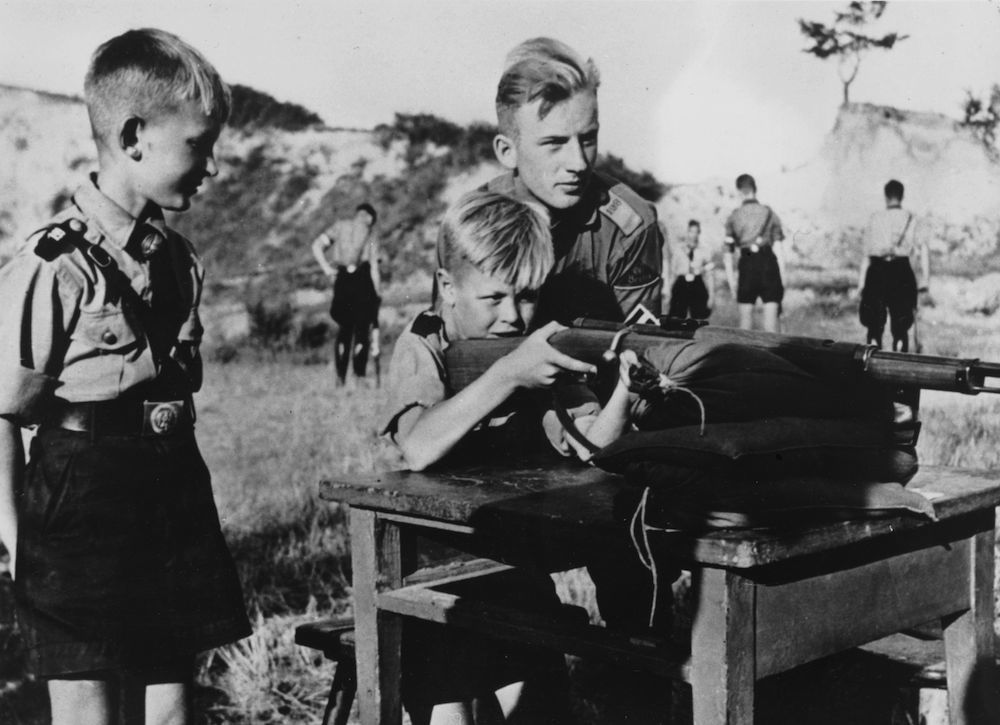 circa 1935: Eleven year old boys in the Hitler Youth organization learning how to fire a rifle. (Photo by Keystone/Getty Images)