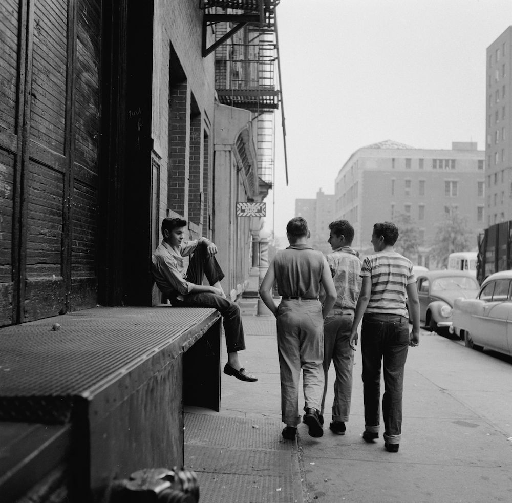 circa 1955: A teenage street gang notice a potential recruit as they walk by a New York tenement building. (Photo by Carl Purcell/Three Lions/Getty Images)