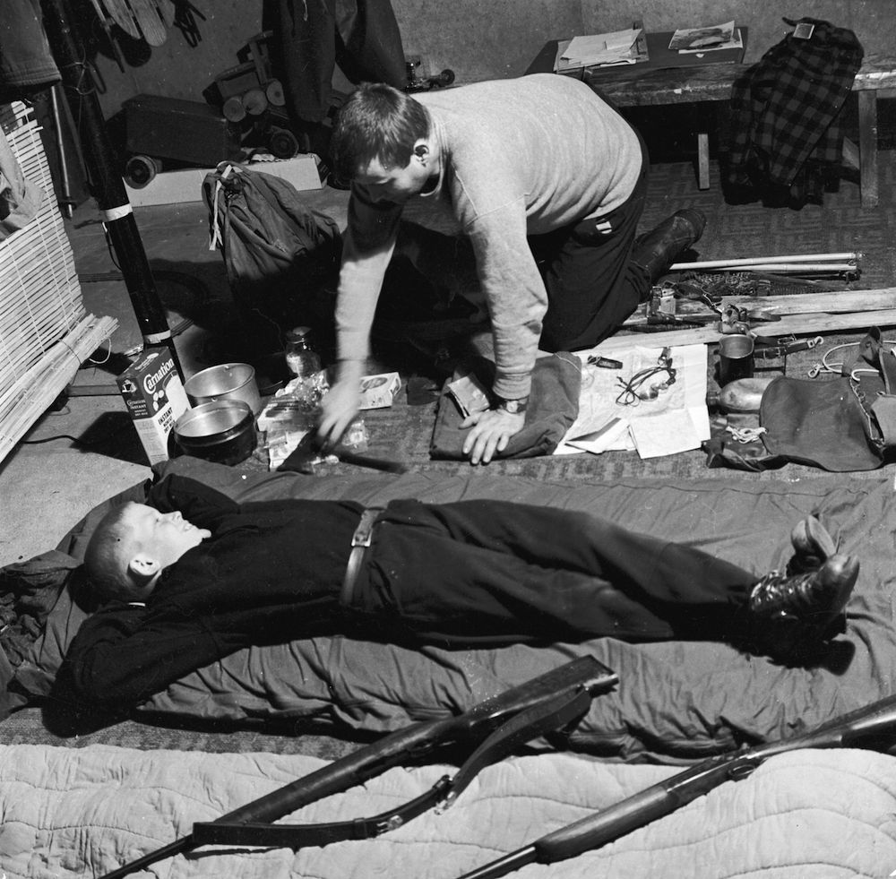 circa 1955: A father and son check their equipment the night before their hunting trip. (Photo by John Titchen/Three Lions/Getty Images)