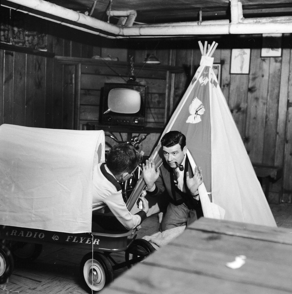 circa 1956: Radio and television announcer (and pipe smoking Indian Chief), Frank Blair, is in a fix as his cowboy gunman son gets the drop on him on Christmas morning. (Photo by Three Lions/Getty Images)