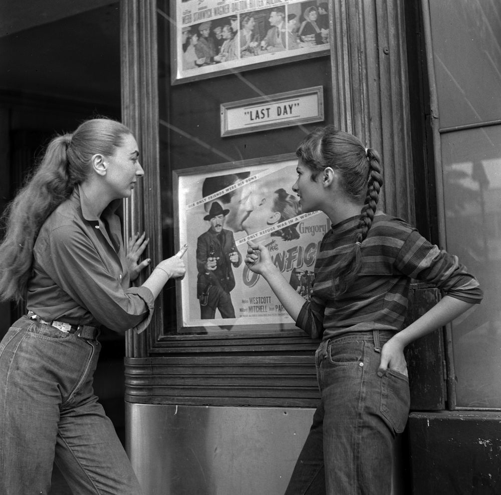 circa 1955: Two members of a teenage girl gang looking at a cinema poster starring one of their movie heroes. (Photo by Vecchio/Three Lions/Getty Images)