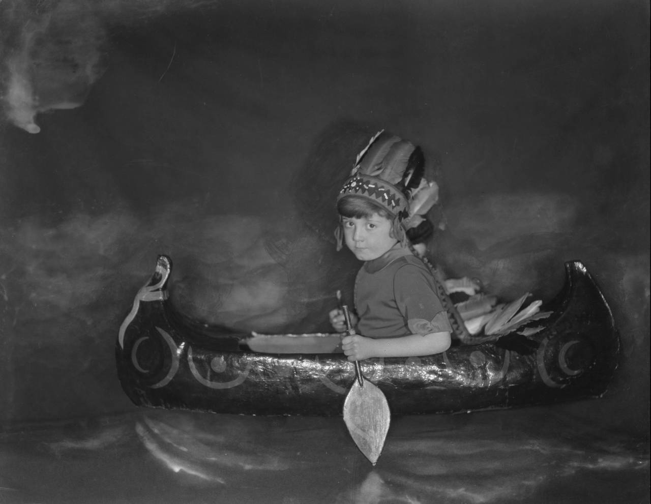 circa 1925: Christopher Robin Milne, immortalized with his toy bear Winnie-the-Pooh in his father A A Milne's children's classics, paddling his toy canoe, dressed as a Native American.