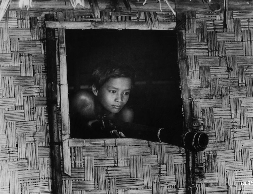 circa 1930: A boy leans out of the window of a bamboo hut, ready to fire his gun.