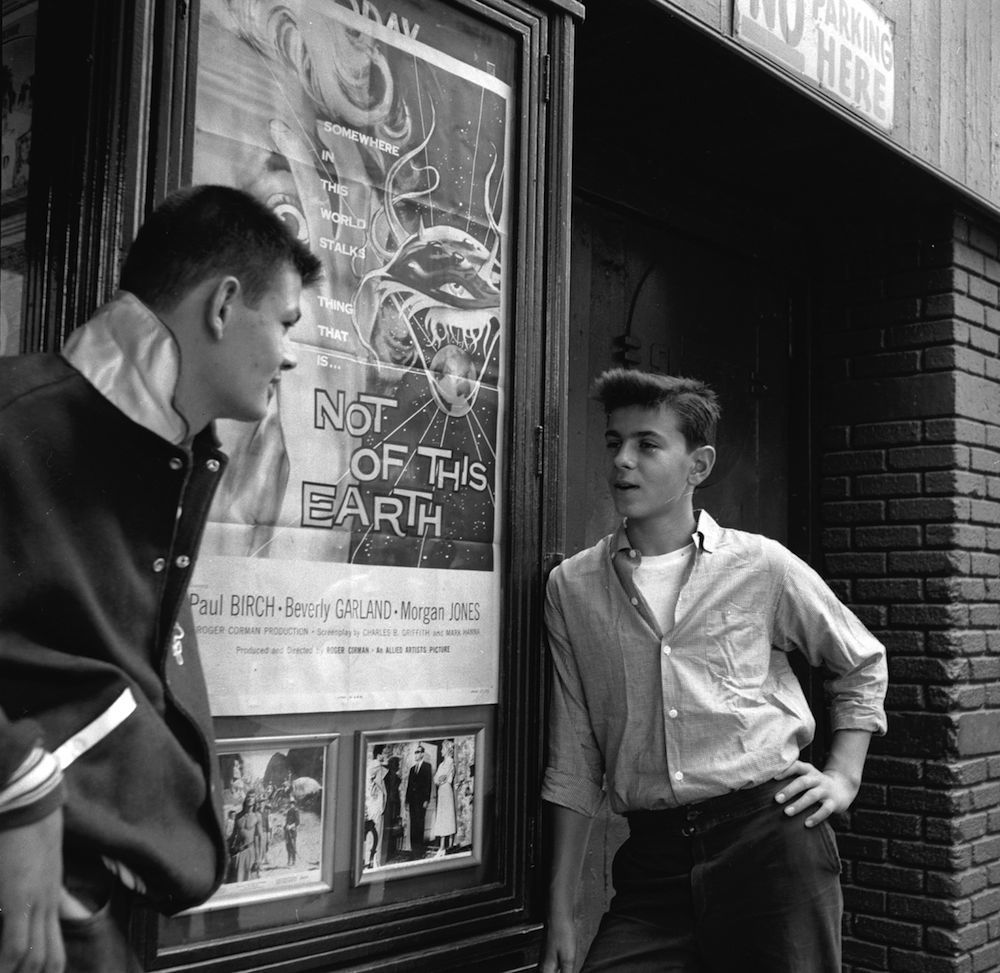circa 1955: Two members of a teenage street gang chat outside a New York cinema showing 'Not Of This Earth'. (Photo by Carl Purcell/Three Lions/Getty Images)