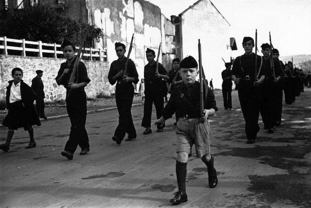 13th November 1936: A youth parade of Spanish schoolchildren makes its way along the road wearing the black shirts of the Fascists and carrying dummy rifles. Their home of Irun has been taken over by Rebel troops during the Spanish Civil War, and they have been converted to the Fascist cause. (Photo by Maeers/Fox Photos/Getty Images)