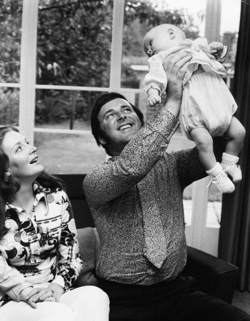 Irish broadcaster Terry Wogan with his wife Helen, holding his baby daughter Katherine in the air at their home, circa 1972. (Photo by Chris Ware/Keystone/Getty Images)