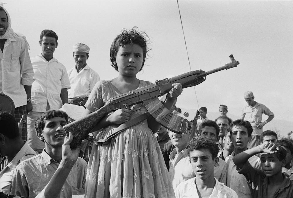 A young girl poses with members of the National Liberation Front (NLF) during the Aden Emergency, Yemen, 1967. (Photo by Stan Meagher/Express/Hulton Archive/Getty Images)