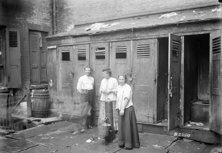Two women & man in front of outhouses; one woman getting water