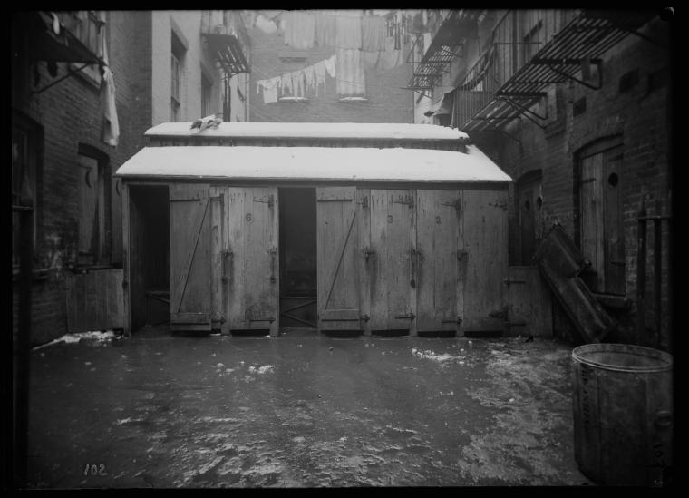 Row of outhouses with laundry and fire escapes (1902).