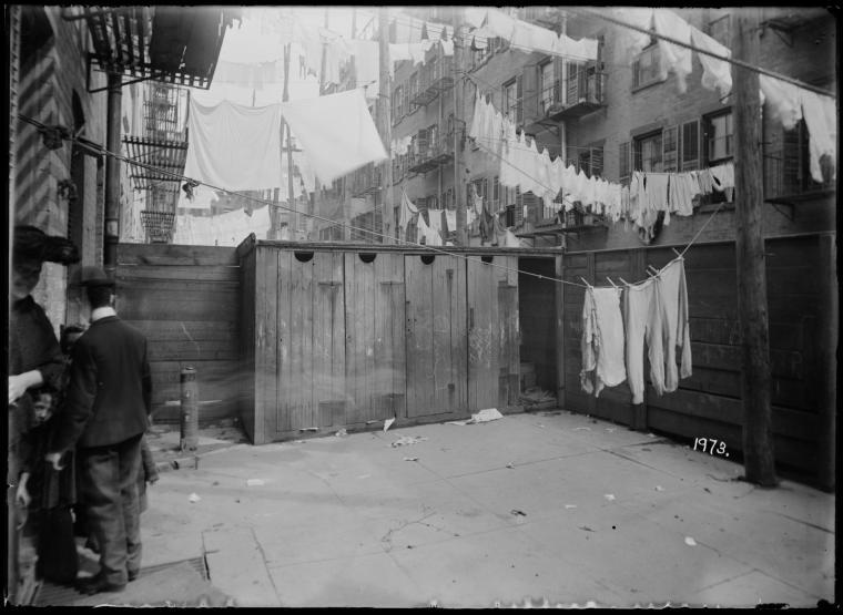Row of outhouses, laundry and backs of tenement…(1904).