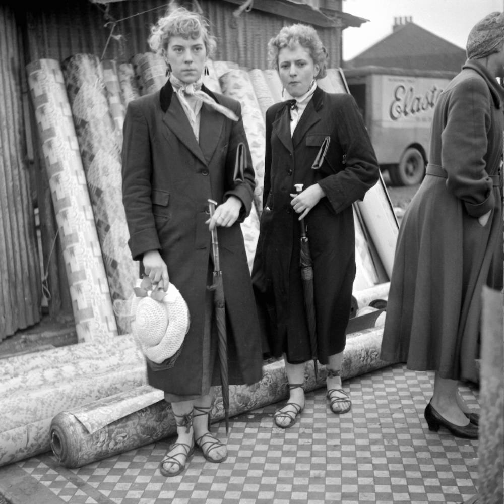 Photo by Ken Russell - January 1955 The last of the Teddy Girls Iris Thornton and Pat Wiles friend standing on some linoleum in front of upright rolls of flooring. ©2006 TopFoto/Ken Russell