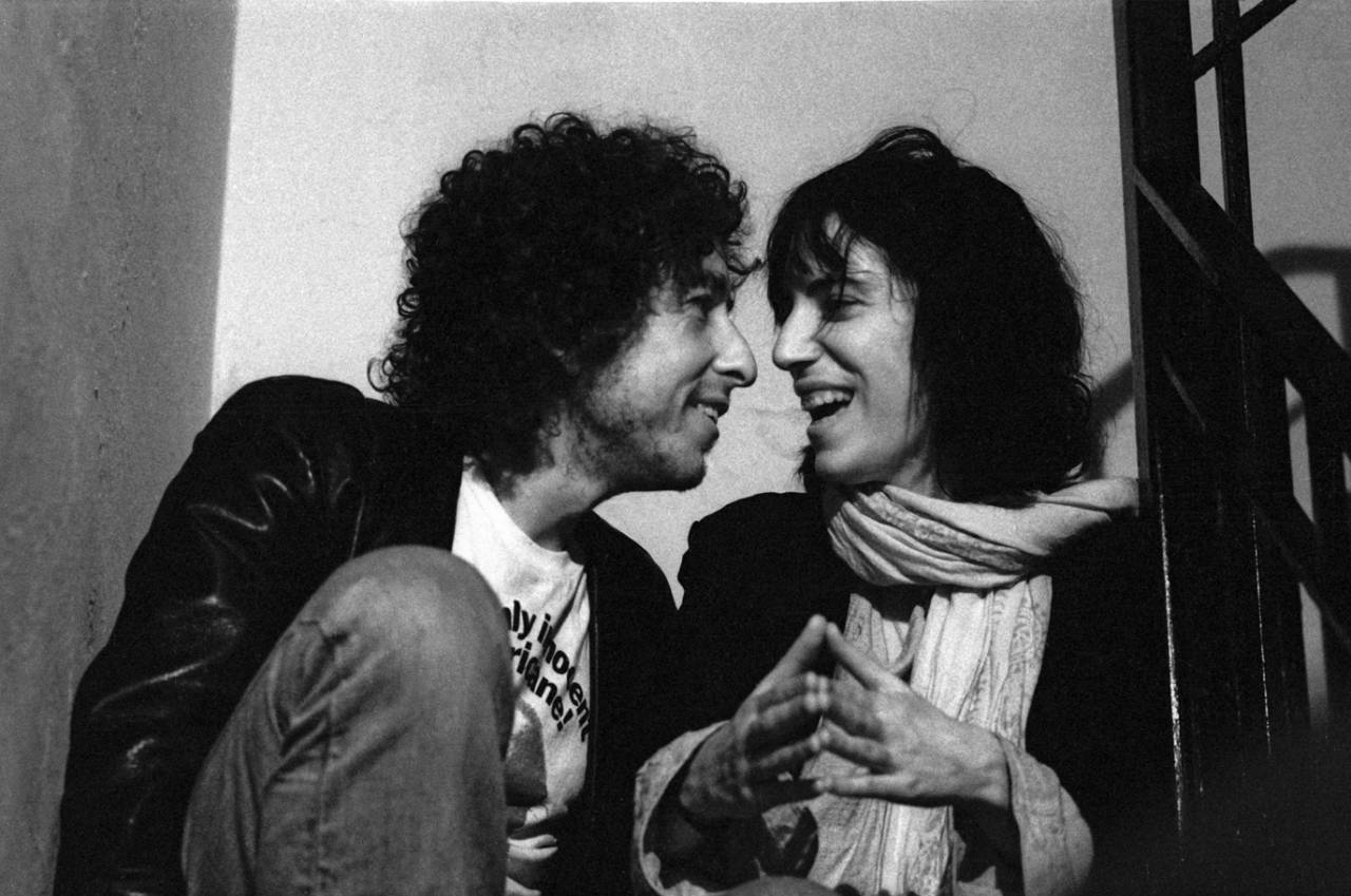 Party in Greenwich Village where Ken takes a famous series of photographs of Patti Smith and Bob Dylan in animated discussion on the stairs.