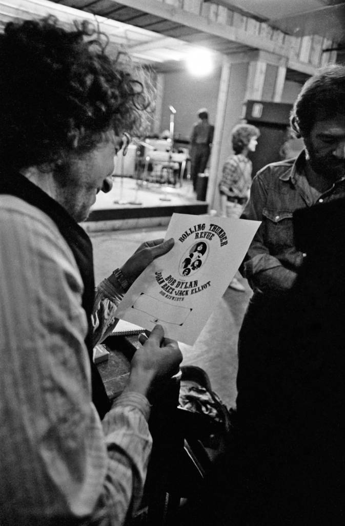 Bob Dylan examining a proof of a flyer for The Rolling Thunder Revue during Ken Regan's first shoot in October 1975, during rehearsals in NYC.