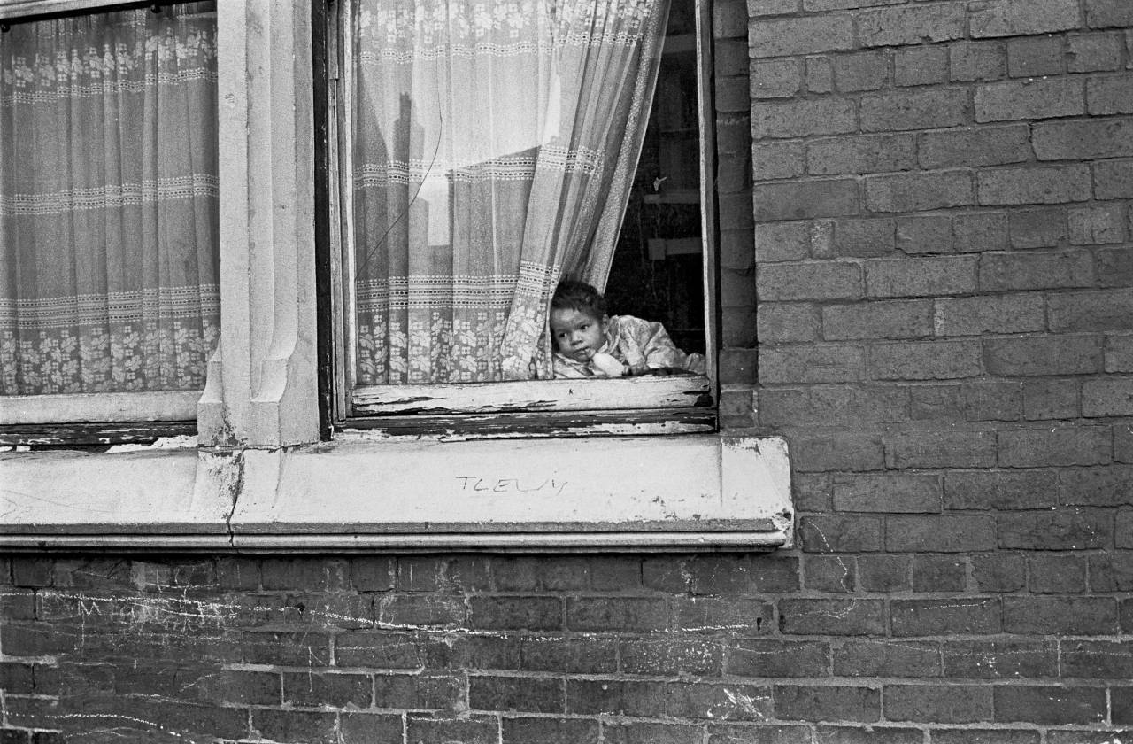 Baby propped in window of Liverpool 8 house 1969