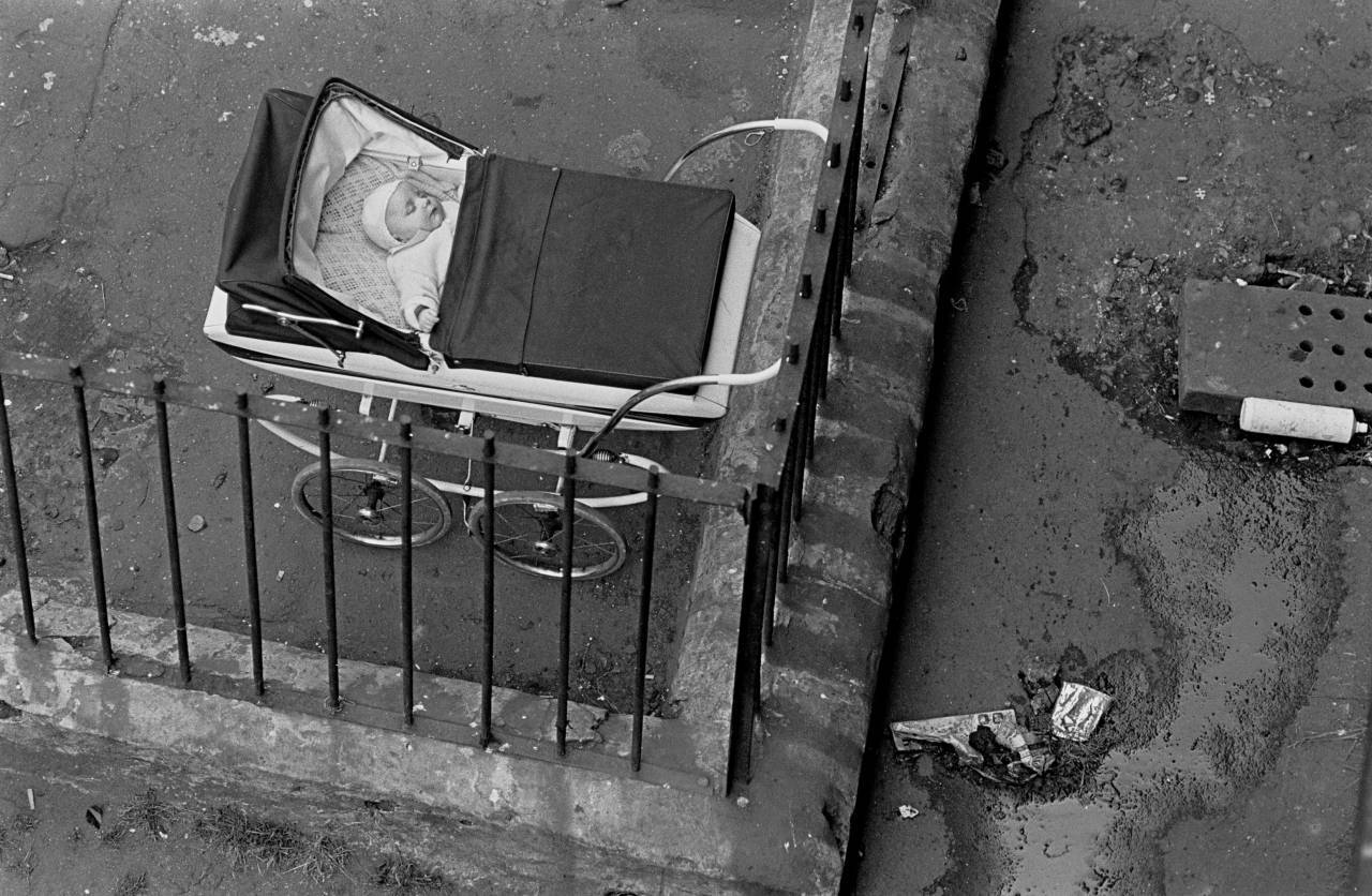 Baby sleeping by the drains in a tenement courtyard Glasgow Maryhill 1971