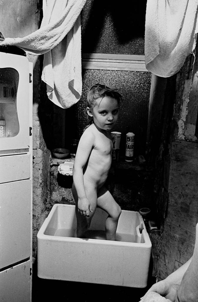Bathtime in the kitchen for Peggy Rump's daughter, Rothschild Dwellings 1969