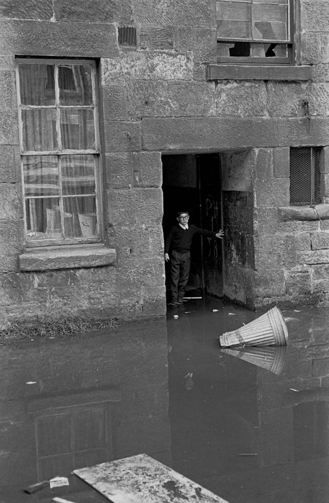 Boy negotiating flooded entry in tenement block Maryhill 1971