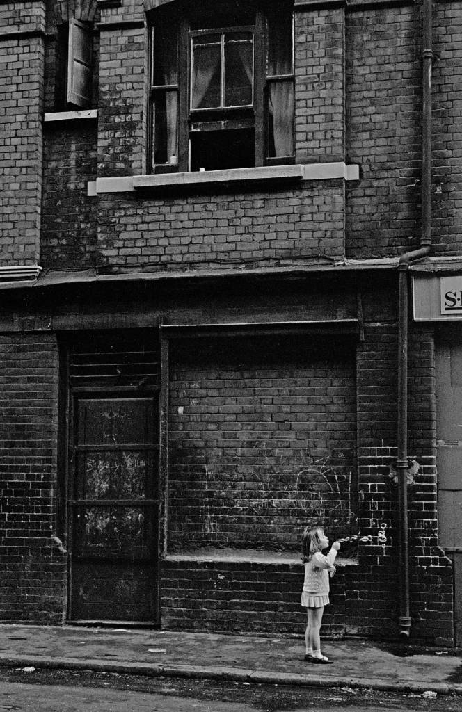 Child blowing bubbles in the street, Whitechapel 1969