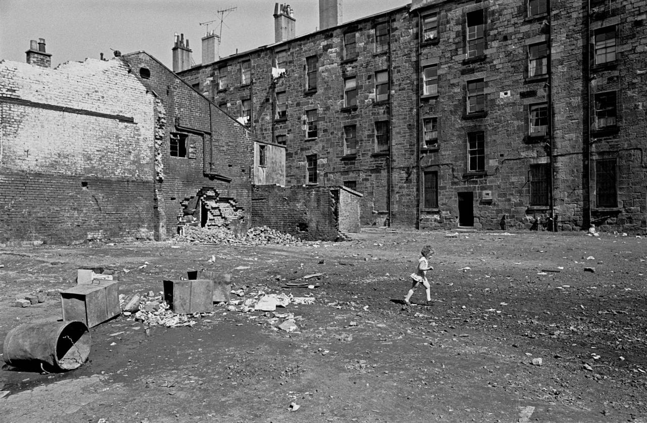 Child crosses a Glasgow tenement courtyard 197