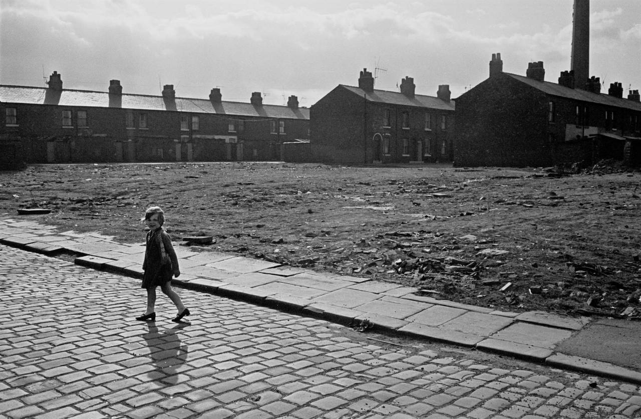 Child crossing waste ground Salford 1969