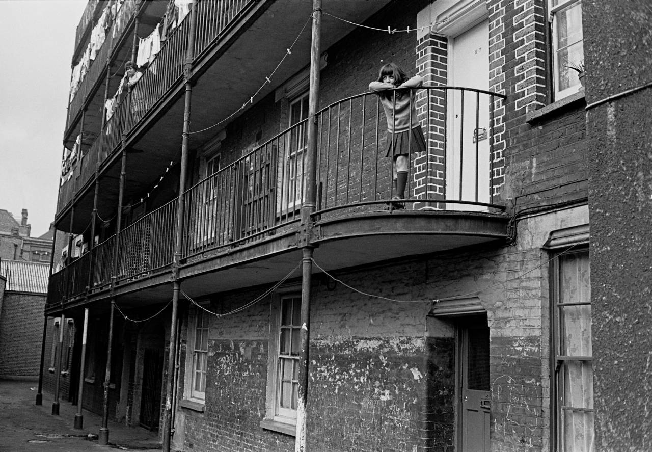 Child dreaming on balcony of her tenement block, Southwark 1970