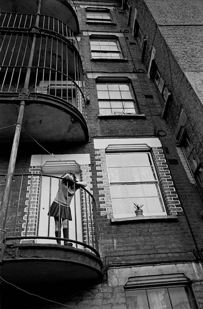 Child on balcony of her tenement block, Southwark 1970
