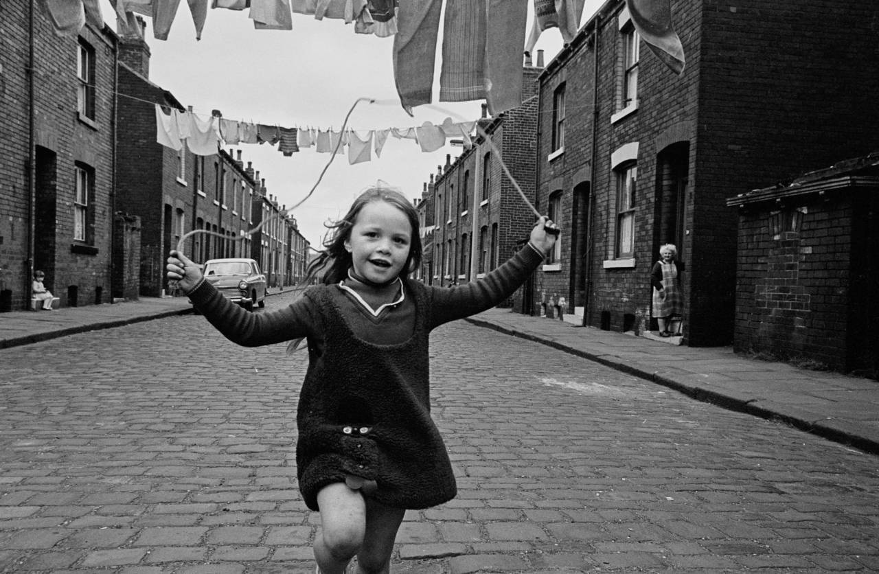 Child skipping in a street of back to back houses, Leeds 1970