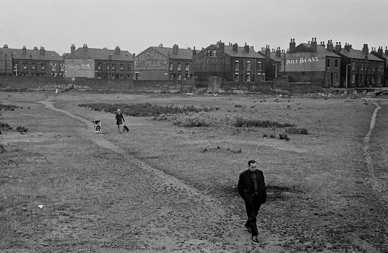 Crossing wasteland from back to back housing towards railway line, Leeds 1970