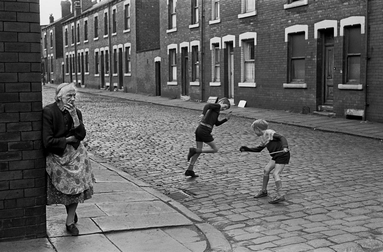 Elderly lady standing at her street corner, back to back housing Leeds 1970