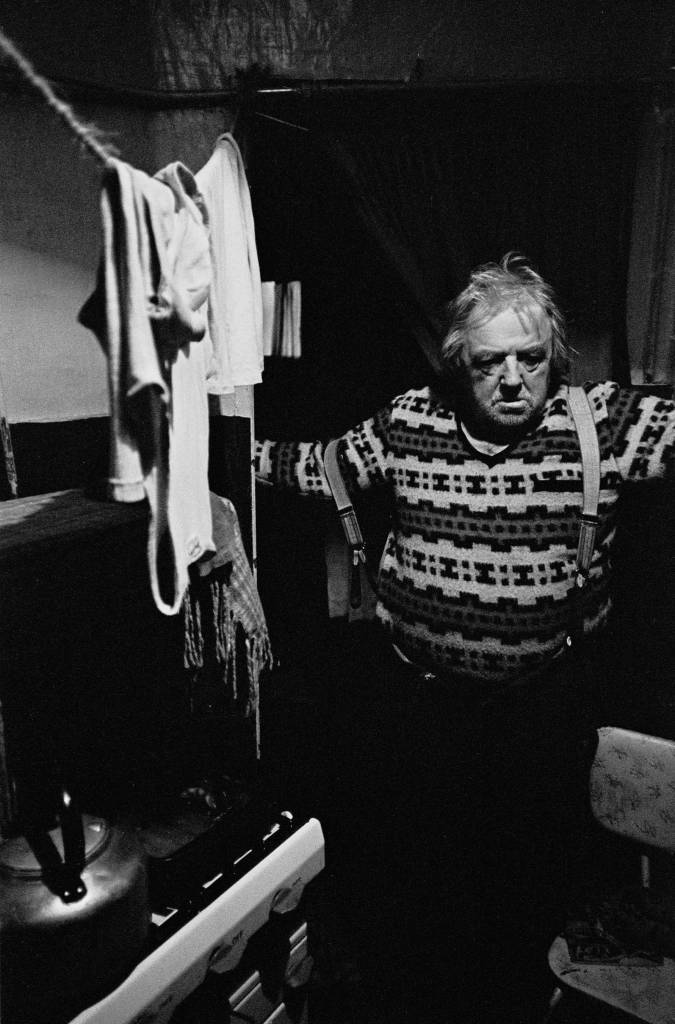 Elderly single man in the kitchen of his basement flat Lambeth 1970