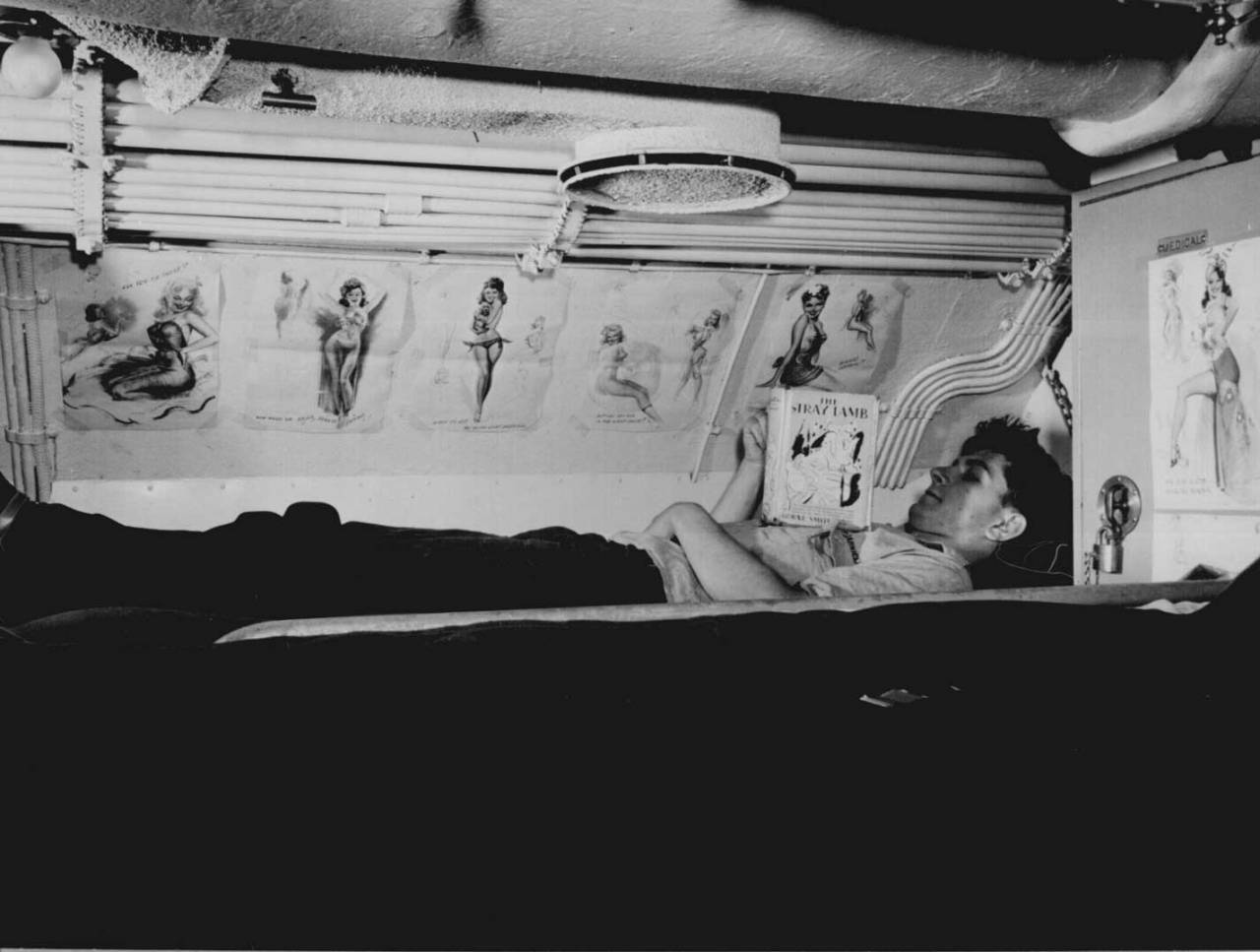 American sailor reading in his bunk aboard USS Capelin, August 1943, United States National Archives