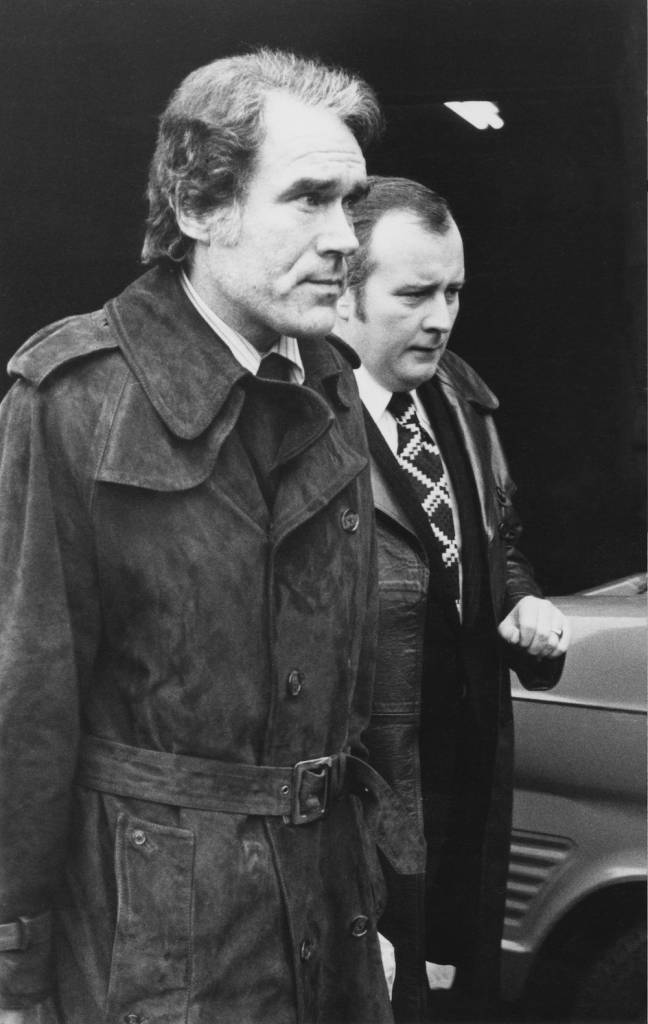 Soho sex club owner Jimmy Humphreys arrives at Heathrow Airport, handcuffed to Detective Sergeant Terence Brown of Scotland Yard (right), 10th January 1974. Humphreys was arrested in Amsterdam and brought back to England to testify against several police officers charged with corruption. (Photo by Keystone/Hulton Archive/Getty Images)