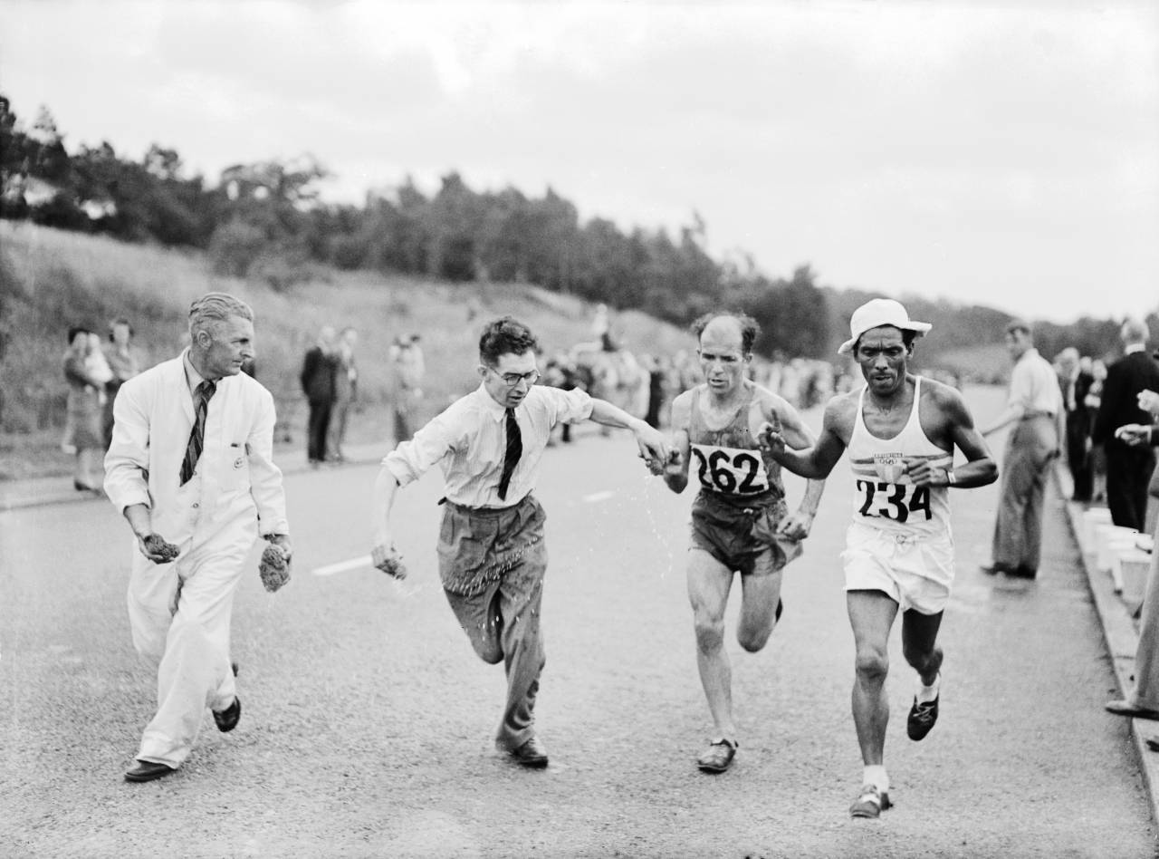 Rene Josset of France (number 262) and Eusebio Guinez of Argentina (number 234) are handed wet sponges to cool them down along the Barnet bypass, during the marathon event at the Olympic Games, London, 7th August 1948. Josset did not finish the race. Guinez finished in 5th place. (Photo by Keystone/Hulton Archive/Getty Images)