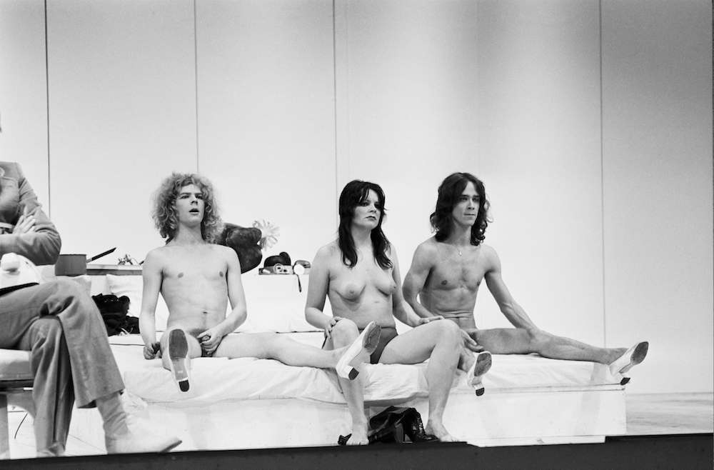 American actress Cherry Vanilla (Kathleen Dorritie, centre) in a scene from Andy Warhol's play 'Pork', 29th July 1971. The scene is being performed at a photocall following a dress rehearsal at the Roundhouse in London. 'Pork' had run for two weeks in New York before being brought to London. Warhol is seated at far left. (Photo by Douglas Miller/Keystone Features/Hulton Archive/Getty Images)