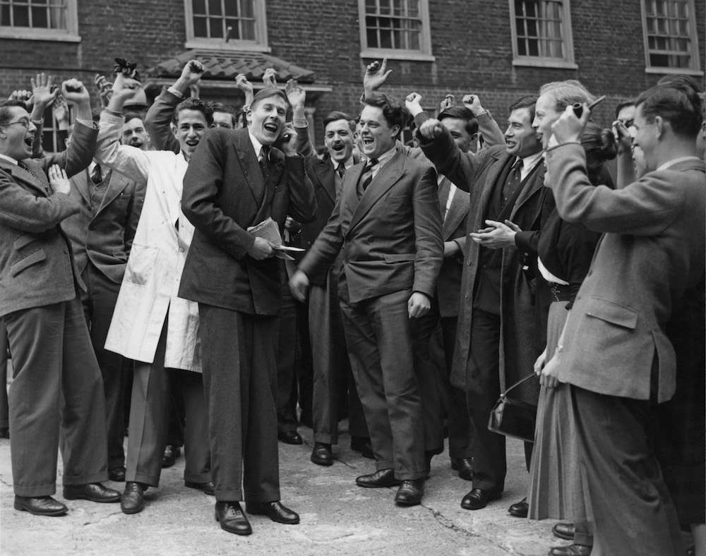English athlete Roger Bannister is cheered by his fellow medical students at St Mary's Hospital, Paddington, the day after he ran his record-breaking sub-four minute mile, London, 7th May 1954. (Photo by Douglas Miller/Keystone/Hulton Archive/Getty Images)