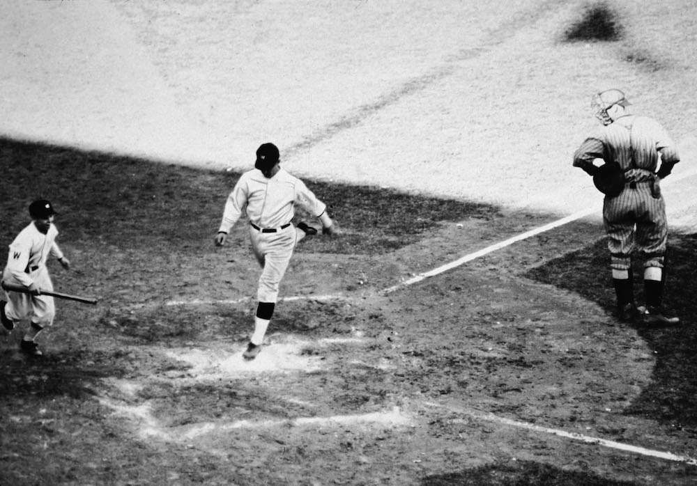 """American baseball player Stanley """"Bucky"""" Harris (1896- 1977), playing for the Washington Senators, lands on home plate after scoring a homerun during the seventh game of the World Series at Griffith Stadium, Washington, D.C., October 10, 1924. Washington won the game and the series. (Photo by Credit: APA/Getty Images)"""