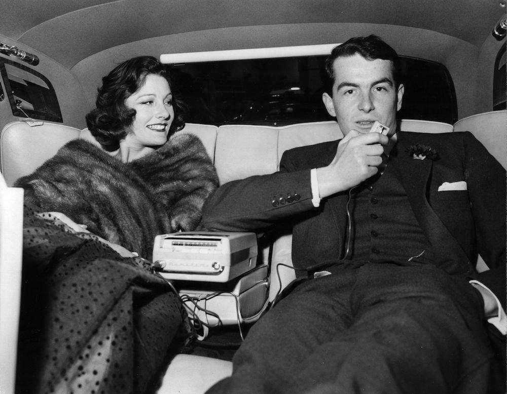 Bronwen Pugh, popular fashion model, in the back of the latest model of a Bentley at the Motor Show Preview at Earls Court. She is with John Fenton, male model and they are making a recording on the built in tape recorder. Original Publication: People Disc - HK0439 (Photo by Keystone/Getty Images)