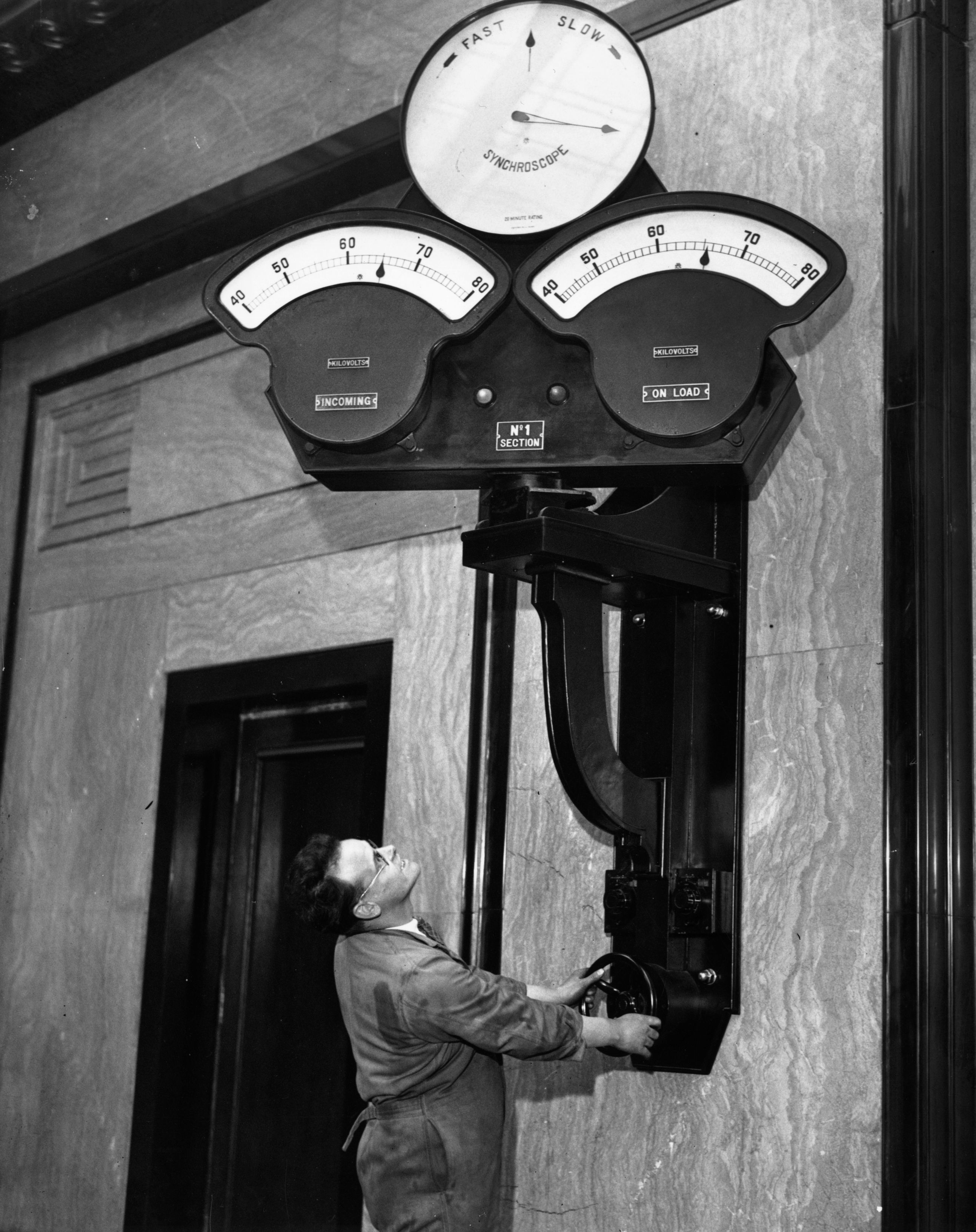 A man operating the controls at Battersea Power Station, London. (Photo by Fox Photos/Getty Images)