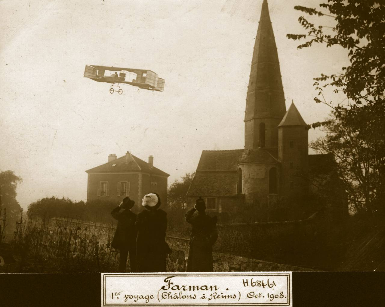 31st October 1908: French aviation pioneer Henri Farman (1874 - 1958) flying over a small village near Reims during his European cross country record flight of 26 kilometres from Chalons to Reims. He is flying a Voisin box-kite aeroplane and is making Europe?s first cross-country flight. Aeroplane Album - Vol 2 Page 9