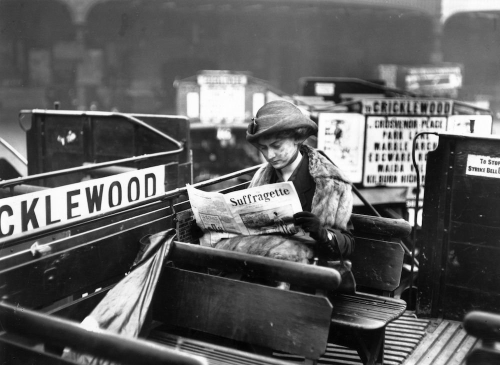 A woman reading a copy of the 'Suffragette' magazine on an open-top London bus. (Photo by Topical Press Agency/Getty Images)