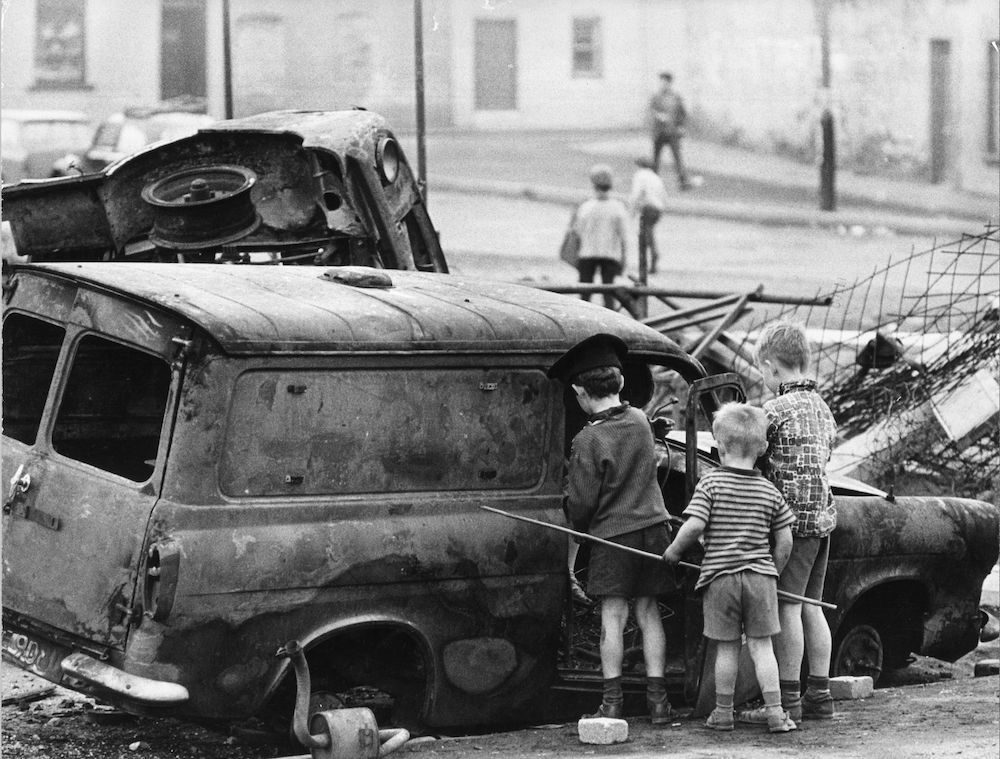 Young children playing with the wreckage of a burnt out car in Belfast. (Photo by Three Lions/Getty Images)