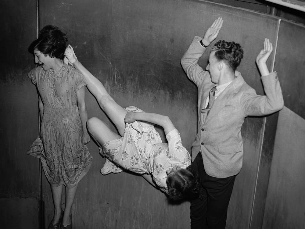 Centrifugal force pins three intrepid people to the wall of the Rotor at the Festival Pleasure Gardens in London. Doris Flores (left) appears to be averting her eyes from Doris Flaxman's immodest display of leg.   (Photo by Don Price/Getty Images)