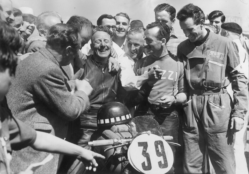 7th June 1951:  Tommy Wood of Southampton being congratulated by Italian riders after winning the International Lightweight TT in the Isle of Man. He rode a 248cc Guzzi and averaged 81.39 mph.  (Photo by Don Price/Fox Photos/Getty Images)