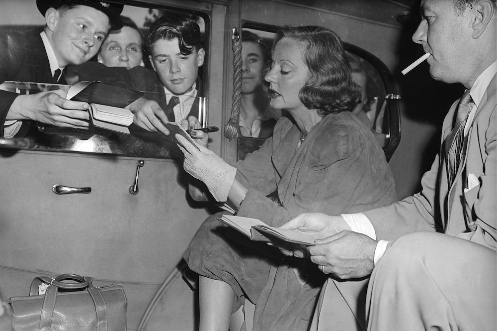 7th  September 1951:  American actress, Tallulah Bankhead (1902 - 1968), signing autographs from the back of her car.  (Photo by Allan/Express/Getty Images)