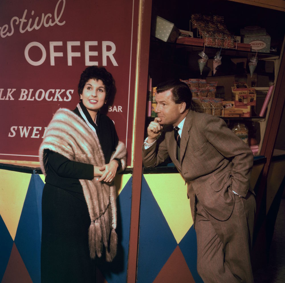 12th May 1956: Film actor Kenneth More (1914 - 1982) and English singer Alma Cogan (1932 - 1966) attend the opening of the Festival Gardens at Battersea, London. (Photo by Hulton Archive/Getty Images)